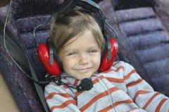 nettes Baby in den Kopfhörern, die im Cockpit eines kleinen t sitzen lizenzfreie stockbilder