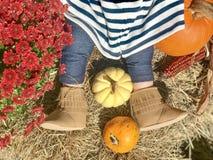 Nettes Baby in den Stiefeln mit Kürbisen im Heu während der Fallherbsterntedankfeste lizenzfreies stockfoto