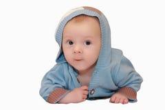 Nettes Baby in der Strickjacke mit der Haube, die auf seinem Magen lokalisiert auf Weiß liegt Stockfotos