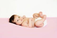 Nettes Baby der Windel, die oben auf seiner Rückseiten- und Erhöhungsbeine liegt stockfotografie