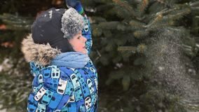 Nettes Baby in der Winterkleidung und -c$tragen eines Hutes vor dem hintergrund des Schnees und eines Weihnachtsbaums stock footage