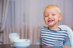 Nettes Baby des Jungen, das Fr?hst?ck Kind isst, Brei zu essen Blaue Augen des Kindernetten Jungen sitzen bei Tisch mit Platte un stockbilder