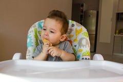 Nettes Baby des Porträts, das Kinderkeks das erste Lebensmittel für Babys 10 Monate isst Kleinkindjunge, der lernt, mit Zahnkörpe Stockfotos
