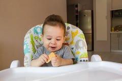Nettes Baby des Porträts, das Kinderkeks das erste Lebensmittel für Babys 10 Monate isst Kleinkindjunge, der lernt, mit Zahnkörpe Lizenzfreies Stockfoto