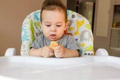 Nettes Baby des Porträts, das Kinderkeks das erste Lebensmittel für Babys 10 Monate isst Kleinkindjunge, der lernt, mit Zahnkörpe Stockfotografie
