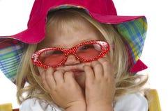 Nettes Baby in einem roten Hut und in den Sonnenbrillen. Stockbild