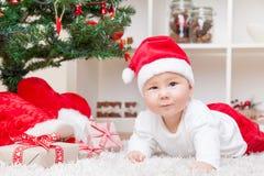 Nettes Baby in einem Sankt-Hut nahe bei Weihnachtsbaum mit Geschenken Lizenzfreie Stockbilder
