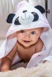 Nettes Baby in einem Tuch, das auf das Sofa kriecht Lizenzfreies Stockfoto