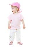 Nettes Baby in einer rosafarbenen Schutzkappe kreischend an jemand Stockbild