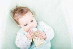 Nettes Baby in einer Trinkmilch der grünen Strickjacke von einer Flasche Lizenzfreie Stockbilder