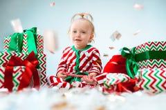 Nettes Baby einjährig nahe Sankt-Hut, der über Weihnachtshintergrund aufwirft Sitzen auf Boden mit Weihnachtsball feiertag stockbilder