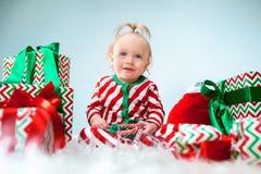 Nettes Baby einjährig nahe Sankt-Hut, der über Weihnachtshintergrund aufwirft Sitzen auf Boden mit Weihnachtsball feiertag lizenzfreies stockbild