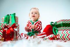 Nettes Baby einjährig nahe Sankt-Hut, der über Weihnachtshintergrund aufwirft Sitzen auf Boden mit Weihnachtsball feiertag stockfotografie
