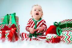 Nettes Baby einjährig nahe Sankt-Hut, der über Weihnachtshintergrund aufwirft Sitzen auf Boden mit Weihnachtsball feiertag lizenzfreie stockbilder