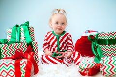 Nettes Baby einjährig nahe Sankt-Hut, der über Weihnachtshintergrund aufwirft Sitzen auf Boden mit Weihnachtsball feiertag stockfoto