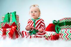 Nettes Baby einjährig nahe Sankt-Hut, der über Weihnachtshintergrund aufwirft Sitzen auf Boden mit Weihnachtsball feiertag lizenzfreie stockfotografie