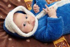 Nettes Baby im blauen Bademantel, der auf Bett liegt Stockbild