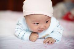 Nettes Baby im Hut auf dem Bett Stockbilder
