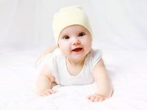 Nettes Baby im Hut auf dem Bett Stockbild