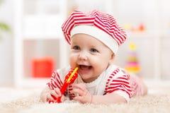 Nettes Baby im Hut auf dem Bett, das Spaß hat Lizenzfreie Stockfotografie