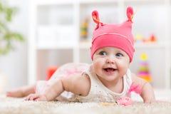 Nettes Baby im Hut auf dem Bett, das Spaß hat Stockbilder