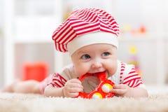 Nettes Baby im Hut auf dem Bett, das Spaß hat Lizenzfreie Stockfotos