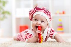 Nettes Baby im Hut auf dem Teppich, der Spaß hat Lizenzfreie Stockfotos