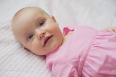 Nettes Baby im rosa Kleid liegt auf weißem backgroun Nahaufnahmeporträt, lächelndes Baby Lizenzfreie Stockbilder