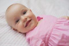 Nettes Baby im rosa Kleid liegt auf weißem backgroun Nahaufnahmeporträt, lächelndes Baby Stockbilder