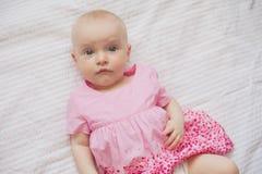 Nettes Baby im rosa Kleid liegt auf weißem backgroun Neugeborenes Kind Stockfoto