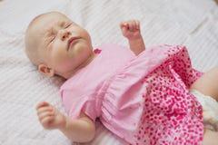 Nettes Baby im rosa Kleid liegt auf weißem backgroun Niesendes Baby Stockfotos