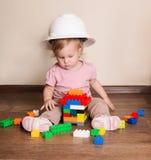 Nettes Baby im Schutzhelm, der mit Plastikerbauer spielt Lizenzfreies Stockbild