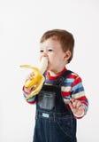 Nettes Baby isst Banane. Stockbilder