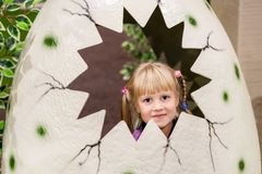 Nettes Baby in künstlichem gebrochenem dinosaurus Ei Kleinkind, das Spaß am Innenspielplatz lächelt und hat stockfoto
