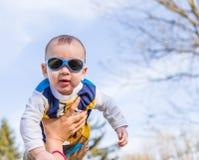 Nettes Baby mit Blau googelt angehoben in einer Luft Stockbilder