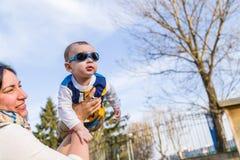 Nettes Baby mit Blau googelt angehoben in einer Luft Stockfotos