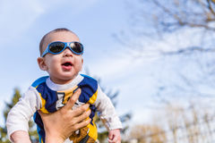 Nettes Baby mit Blau googelt angehoben in einer Luft Lizenzfreies Stockbild