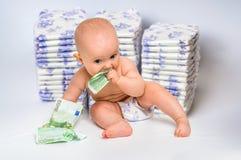 Nettes Baby mit dem Geld lokalisiert auf undeutlichem Windelhintergrund Lizenzfreie Stockbilder