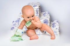 Nettes Baby mit dem Geld lokalisiert auf undeutlichem Windelhintergrund Stockfotografie