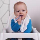Nettes Baby mit dem Löffel, der im Babystuhl sitzt Lizenzfreie Stockfotografie
