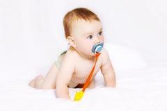 Nettes Baby mit Friedensstifter auf dem Bett Lizenzfreies Stockfoto
