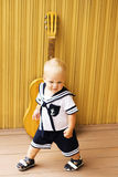 Nettes Baby mit Gitarre gegen hölzerne Wand stockfotos
