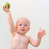 Nettes Baby mit grünem Apfel Stockfoto