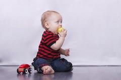 Nettes Baby mit großen Augen, das einen Apfel isst Stockfotos