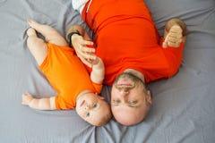 Nettes Baby mit seinem Vater, der Kamera betrachtet Lizenzfreie Stockbilder