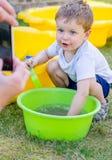 Nettes Baby spielt mit Wasser und der Aufstellung Stockbild
