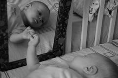 Nettes Baby und Spiegel b&w Stockfotos