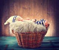Nettes Baby, welches das gestrickte lustige Kostüm, schlafend in einem Korb über hölzernem Hintergrund trägt Stockbild