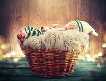 Nettes Baby, welches das gestrickte lustige Kostüm, schlafend in einem Korb über hölzernem Hintergrund trägt Stockfotografie