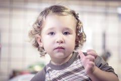 Nettes Baby wirft für ein Foto in der Küche auf Lizenzfreie Stockbilder